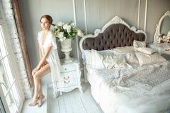 Den unga kvinnan snör åt in damunderklädersammanträde på sängkabinettet i lyx in royaltyfri foto