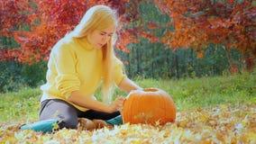 Den unga kvinnan snider en pumpa Sitta i gården i bakgrunden av att gulna träd stock video