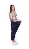 Den unga kvinnan som är lycklig av viktförlust, bantar resultat som isoleras Royaltyfri Bild