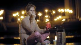 Den unga kvinnan som äter fransman, steker i natten utomhus vid ljuset av lyktor lager videofilmer