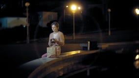 Den unga kvinnan som äter fransman, steker i natten utomhus vid ljuset av lyktor arkivfilmer