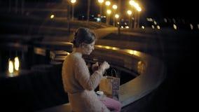 Den unga kvinnan som äter fransman, steker i natten utomhus vid ljuset av lyktor stock video