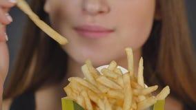 Den unga kvinnan som äter fransman, steker tätt detaljen arkivfilmer