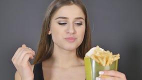 Den unga kvinnan som äter fransman, steker tätt detaljen stock video