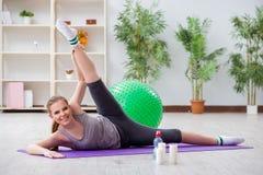 Den unga kvinnan som övar med stabilitetsbollen i idrottshall royaltyfri fotografi