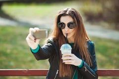Den unga kvinnan som använder en telefon, gör selfie Royaltyfria Bilder