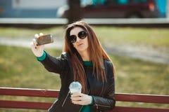 Den unga kvinnan som använder en telefon, gör selfie Arkivbild