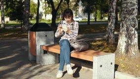 Den unga kvinnan som använder smartphonen i stad, parkerar lager videofilmer