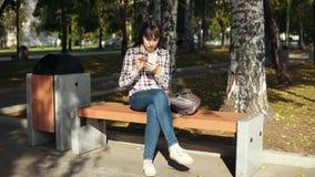 Den unga kvinnan som använder smartphonen i stad, parkerar arkivfilmer
