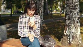 Den unga kvinnan som använder smartphonen i stad, parkerar stock video