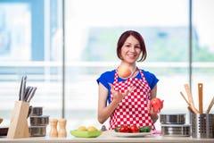 Den unga kvinnan som arbetar i köket Royaltyfri Bild