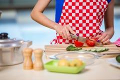 Den unga kvinnan som arbetar i köket Royaltyfri Fotografi