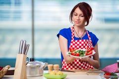 Den unga kvinnan som arbetar i köket Royaltyfria Foton