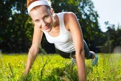 Den unga kvinnan som att göra skjuter, ups på gräs. Royaltyfri Fotografi