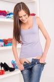 Den unga kvinnan som bär eller, tar av jeans Royaltyfria Foton