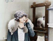 Den unga kvinnan som bär en räv, stal på hennes skuldror och att justera hennes örhänge (alla visade personer inte är längre uppe Arkivfoto