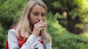 Den unga kvinnan som bär den röda halsduken som besprutar anseende för nasal sprej i staden, parkerar Begrepp för hälsovårdterapi arkivfilmer