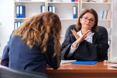 Den unga kvinnan som bes?ker den kvinnliga advokaten fotografering för bildbyråer