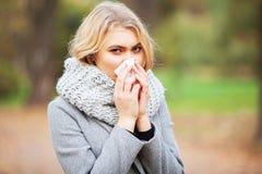 Den unga kvinnan som blåser hennes näsa på, parkerar Utomhus- nysa för kvinnastående därför att förkylning och influensa arkivbild