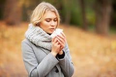 Den unga kvinnan som blåser hennes näsa på, parkerar Utomhus- nysa för kvinnastående därför att förkylning och influensa royaltyfria foton