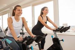 Den unga kvinnan som cyklar i idrottshallen som övar lägger benen på ryggen göra cardio wor Fotografering för Bildbyråer