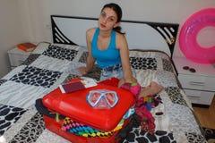 Den unga kvinnan som drömmer av en världstur, sitter nära den öppna resväskan Royaltyfria Bilder