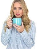 Den unga kvinnan som dricker kaffe från en blått, rånar Fotografering för Bildbyråer