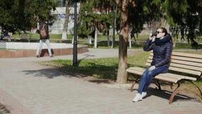 Den unga kvinnan som dricker kaffe på en bänk i det soligt, parkerar lager videofilmer