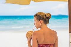 Den unga kvinnan som dricker kokosnöten, mjölkar på schäslong på stranden Fotografering för Bildbyråer