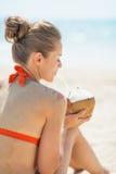 Den unga kvinnan som dricker kokosnöten, mjölkar på stranden arkivfoto