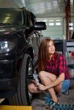 Den unga kvinnan som en mekaniker i kontrollerad skjorta skruva av hjulet med det pneumatiska hjälpmedlet för luft Arkivfoton