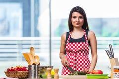 Den unga kvinnan som förbereder sallad i köket Arkivbilder