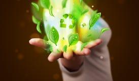 Den unga kvinnan som framlägger det gröna bladet för ecoen, återanvänder energibegrepp Fotografering för Bildbyråer