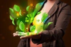 Den unga kvinnan som framlägger det gröna bladet för ecoen, återanvänder energibegrepp Royaltyfria Foton