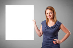 Den unga kvinnan som framlägger pappers- vit, kopierar utrymme arkivfoton