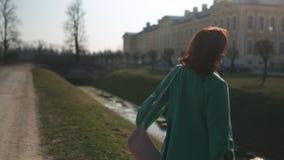 Den unga kvinnan som framme dansar av en slott och den, är kanalen under solen som bär det gröna omslaget och att le för mode stock video