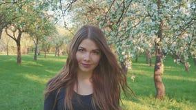 Den unga kvinnan som går i en äpplefruktträdgård blommar på våren, vit Stående av en härlig flicka i aftonfrukten stock video
