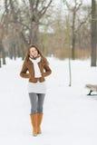 Den unga kvinnan som går i vinter, parkerar Arkivbilder
