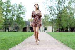 den unga kvinnan som går på sommaren, parkerar royaltyfri fotografi
