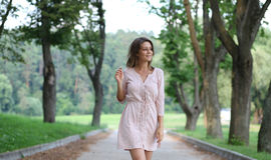 Den unga kvinnan som går på sommaren, parkerar fotografering för bildbyråer