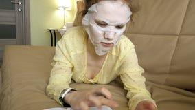 Den unga kvinnan som gör den ansikts- maskeringsmaskeringen med att rentvå maskeringen, klickar på soffan med den hemmastadda sma Arkivfoto