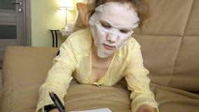 Den unga kvinnan som gör den ansikts- maskeringsmaskeringen med att rentvå maskeringen, klickar på soffan med den hemmastadda sma Arkivbilder