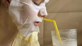 Den unga kvinnan som gör den ansikts- maskeringsmaskeringen med att rentvå maskeringen, klickar på soffan med den hemmastadda sma Royaltyfria Bilder