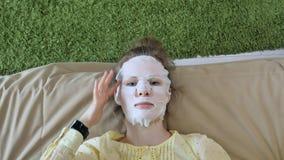 Den unga kvinnan som gör den ansikts- maskeringsmaskeringen med att rentvå maskeringen, klickar på soffan med den hemmastadda sma Arkivbild