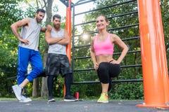 Den unga kvinnan som gör bulgar, squats under konditiongatagenomkörare Fotografering för Bildbyråer