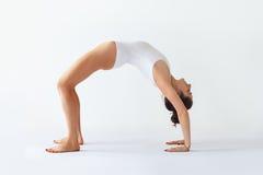 Den unga kvinnan som gör hjulet för pilbågen för yogaasanaen det uppåtriktade, poserar arkivfoton