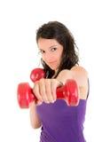 Den unga kvinnan som gör kondition, övar, räcker väger. arkivfoton