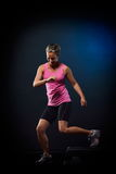 Den unga kvinnan som gör moment, övar i idrottshallen Arkivbilder