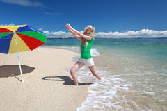 Den unga kvinnan som gör sträckning, övar på stranden royaltyfri fotografi