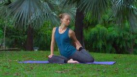Den unga kvinnan som gör yoga, övar i ett tropiskt parkerar lager videofilmer